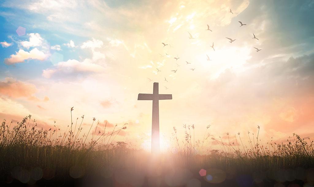 The cross on meadow autumn sunrise background