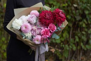 Girl holds pink and purple toned bouquet in vintage style outdoors opposite of the park,